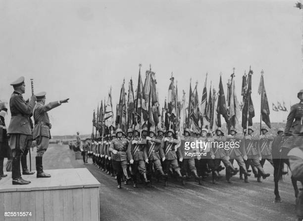 German Chancellor Adolf Hitler takes the salute from his troops, after a staged battle between camouflaged tanks and anti-tank companies on the...