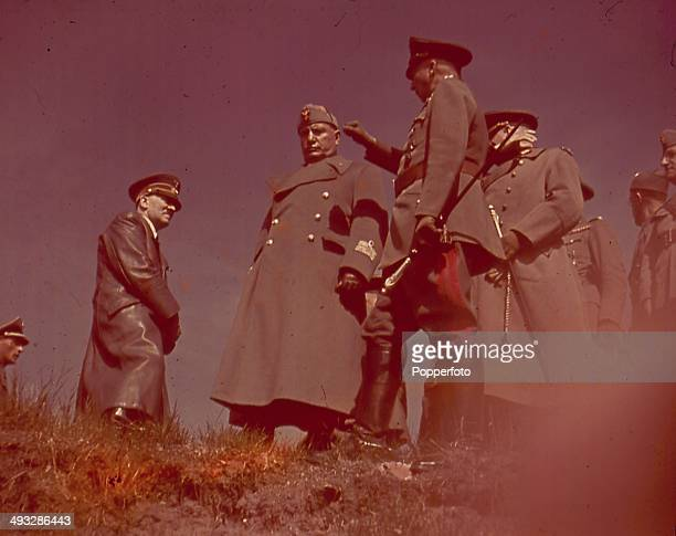 German Chancellor Adolf Hitler talks with Italian Prime Minister Benito Mussolini and German Field Marshal Gunther von Kluge commander of the 4th...