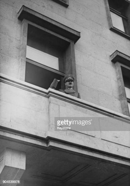 German Chancellor Adolf Hitler waves to the crowds from the window of the new Reich Chancellery building in Berlin Germany January 1939