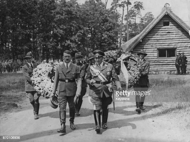 German Chancellor Adolf Hitler with Hermann Goering , and a procession of men carrying wreaths, 1934.