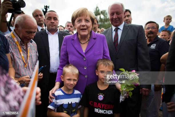 German Chancellor and Chairwoman of the German Christian Democrats Angela Merkel and top candidate Eckhardt Rehberg are welcomed by supporter during...