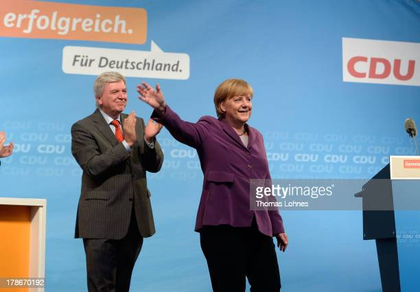 German Chancellor and Chairwoman of the German Christian Democrats Angela Merkel and the prime minister of Hesse Volker Bouffier greet supporters at...
