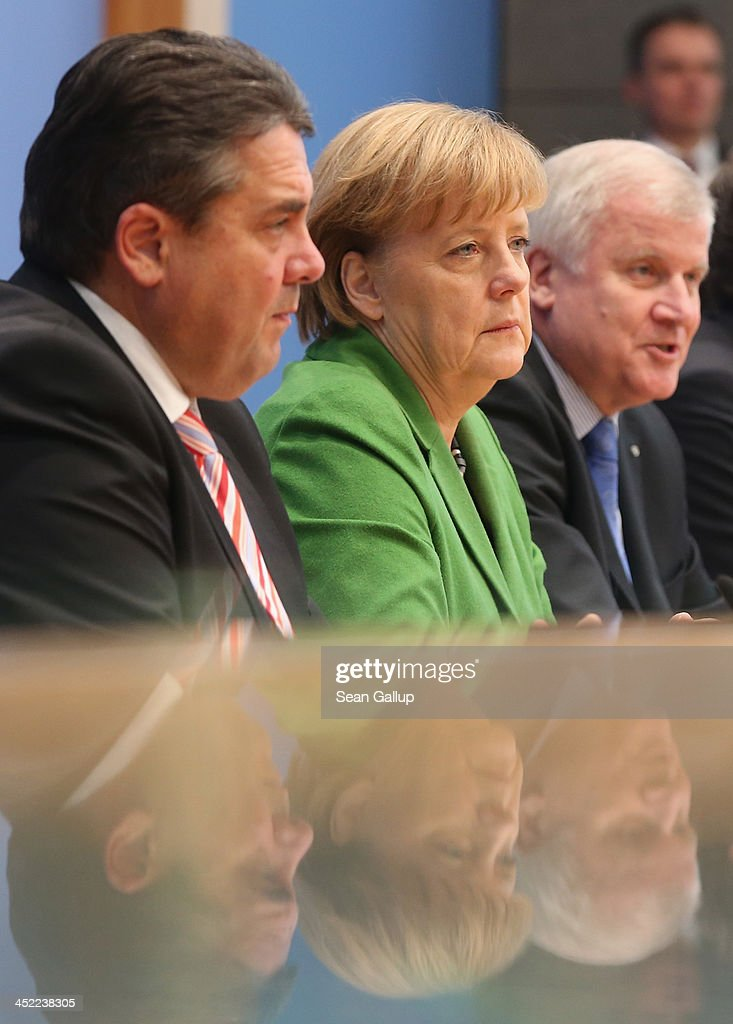 German Chancellor and Chairwoman of the German Christian Democrats (CDU) Angela Merkel (C), Chairman of the German Social Democrats (SPD) Sigmar Gabriel (L) and Chairman of the Bavarian Christian Democrats (CSU) Horst Seehofer discuss the three parties' coalition contract with the media after signing it earlier in the day on November 27, 2013 in Berlin, Germany. The three parties worked their way through arduous negotiations on policy issues that concluded with a 17-hour overnight session last night in order to hammer out the final details that will make a new German coalition government possible. The agreement still requires approval by party delegates, which especially in the case of the SPD is uncertain.