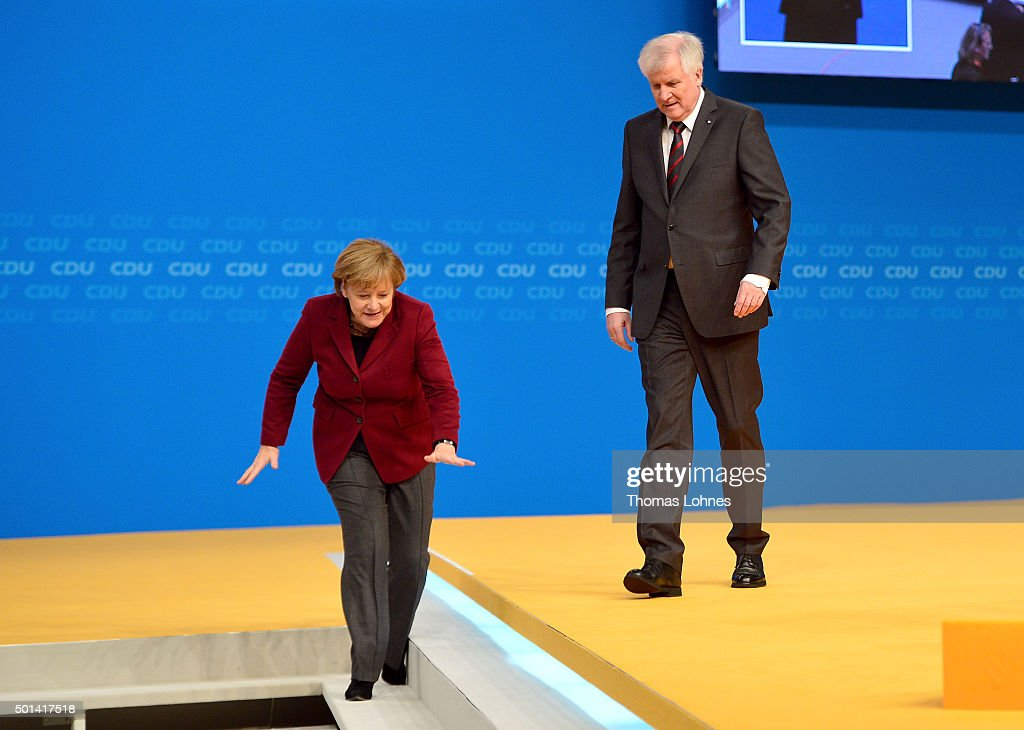 German Chancellor and Chairwoman of the German Christian Democrats (CDU) Angela Merkel and Horst Seehofer, Head of Bavarian Christian Democrats (CSU) and Governeur of Bavaria leave the stage after the speech of Seehofer at the annual CDU federal congress on December 15, 2015 in Karlsruhe, Germany. The CDU is meeting following a dramatic year in which Germany admitted approximately one million migrants and refugees under an open-door policy spearheaded by Merkel. A growing number of CDU members think Merkel has gone too far and see the influx as a burdensome challenge that should have been capped sooner.