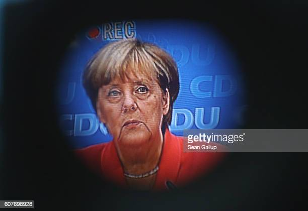 German Chancellor and Chairwoman of the German Christian Democrats Angela Merkel is seen in the ocular of a television camera while she spoke to the...