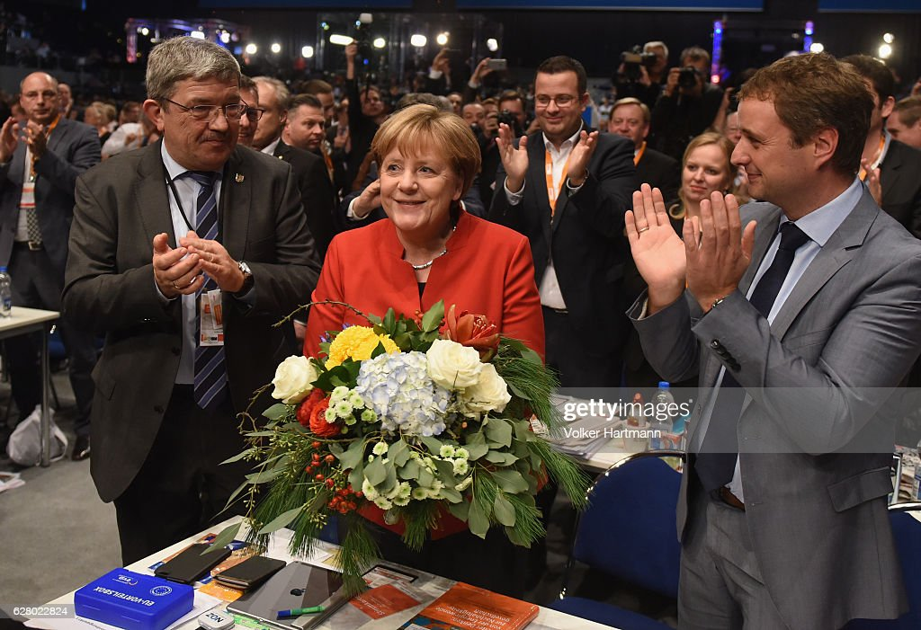 German Chancellor and Chairwoman of the German Christian Democrats (CDU) Angela Merkel (C) receives applause after she was re-elected by delegates as party chairwoman at the 29th federal congress of the CDU on December 6, 2016 in Essen, Germany. Approximately 1,000 CDU delegates are meeting to debate and vote on the party's course for next year following the recent announcement by Merkel that she will run for a fourth term as chancellor in federal elections scheduled for next September.