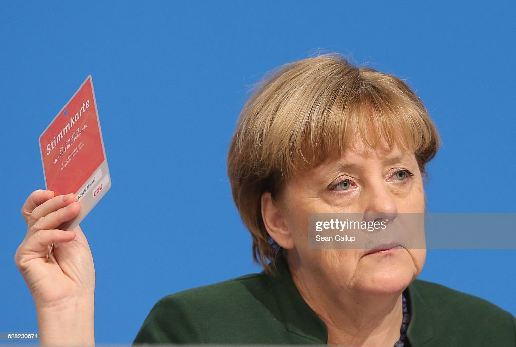 German Chancellor and Chairwoman of the German Christian Democrats (CDU) Angela Merkel holds up her voting card to vote on a proposal at the 29th federal congress of the CDU on December 7, 2016 in Essen, Germany. Approximately 1,000 CDU delegates are meeting to debate and vote on the party's course for next year following the recent announcement by Merkel that she will run for a fourth term as chancellor in federal elections scheduled for next September.