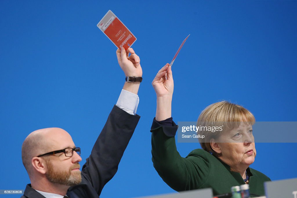 German Chancellor and Chairwoman of the German Christian Democrats (CDU) Angela Merkel and her colleague Peter Tauber hold up their voting card to vote on a proposal at the 29th federal congress of the CDU on December 7, 2016 in Essen, Germany. Approximately 1,000 CDU delegates are meeting to debate and vote on the party's course for next year following the recent announcement by Merkel that she will run for a fourth term as chancellor in federal elections scheduled for next September.
