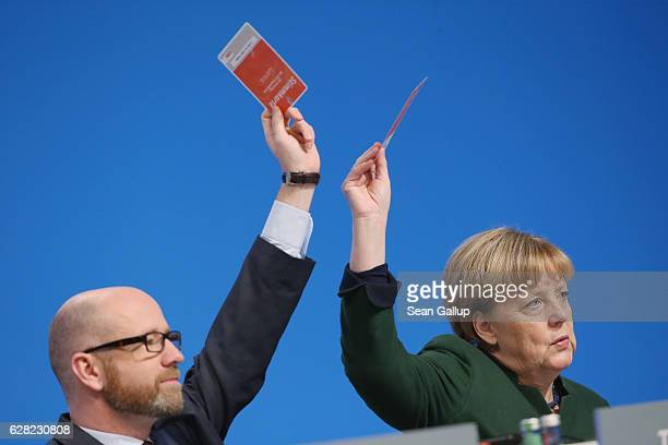 German Chancellor and Chairwoman of the German Christian Democrats Angela Merkel and her colleague Peter Tauber hold up their voting card to vote on...