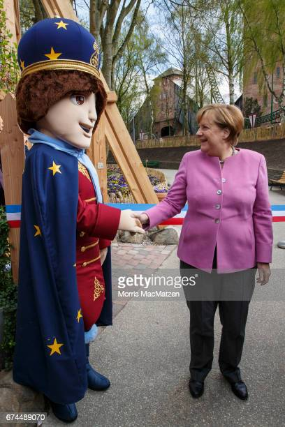 German Chancellor and Chairwoman of the German Christian Democrats Angela Merkel greets the 'Little Zar'mascot as she opens a roller coaster for...