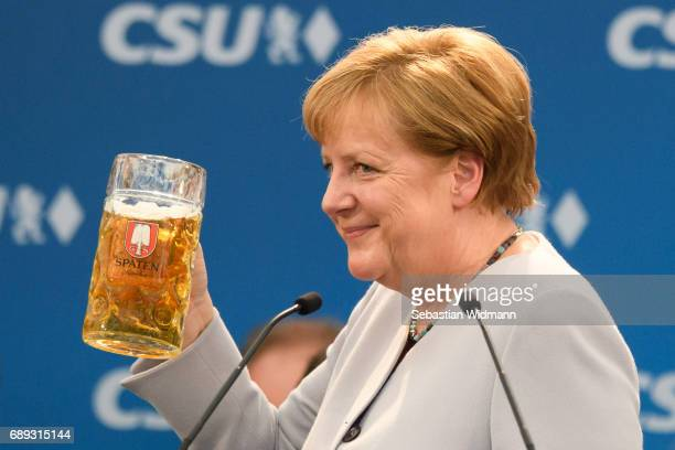 German Chancellor and Chairwoman of the German Christian Democrats Angela Merkel holds a beer mug after her speech at the Trudering fest on May 28...