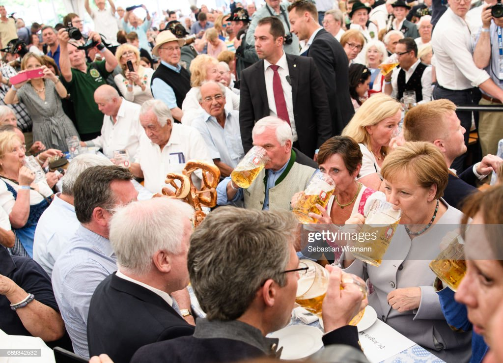 German Chancellor and Chairwoman of the German Christian Democrats (CDU) Angela Merkel drinks from a beer mug at the Trudering fest on May 28, 2017 in Munich, Germany. The CDU and CSU, along with the German Social Democrats (SPD), form the current German coalition government, though relations between Merkel and Seehofer have been complicated as the two have clashed over certain issues, especially immigration.