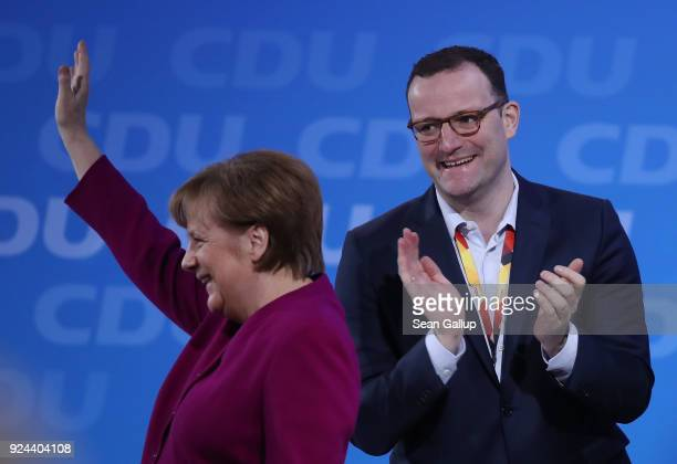 German Chancellor and Chairwoman of the German Christian Democrats Angela Merkel waves to delegates as her colleague Jens Spahn who has been an...