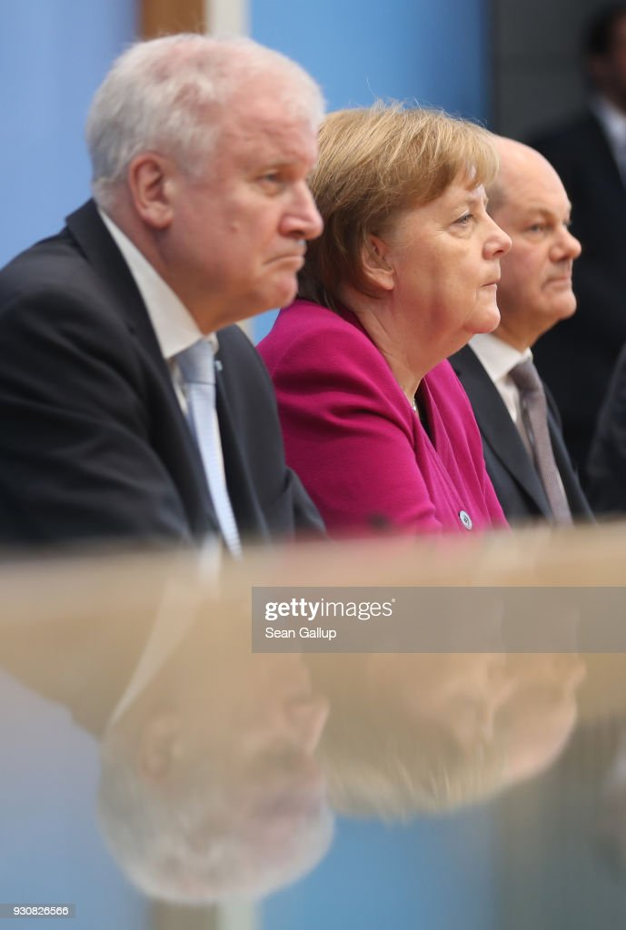 German Chancellor and Chairwoman of the German Christian Democrats (CDU) Angela Merkel (C), Acting Chairman of the German Social Democrats (SPD) Olaf Scholz (R) and Chairman of the Bavarian Christian Democrats (CSU) Horst Seehofer are reflected in glas as they speak to the media prior to this afternoon's signing of the coalition contract by the CDU, SPD and CSU on March 12, 2018 in Berlin, Germany. The German Christian Democrats (CDU), the German Social Democrats (SPD) and the Bavarian Christian Democrats (CSU) will sign the coalition contract that will create the next German government. The new government will be sworn in this coming Wednesday.
