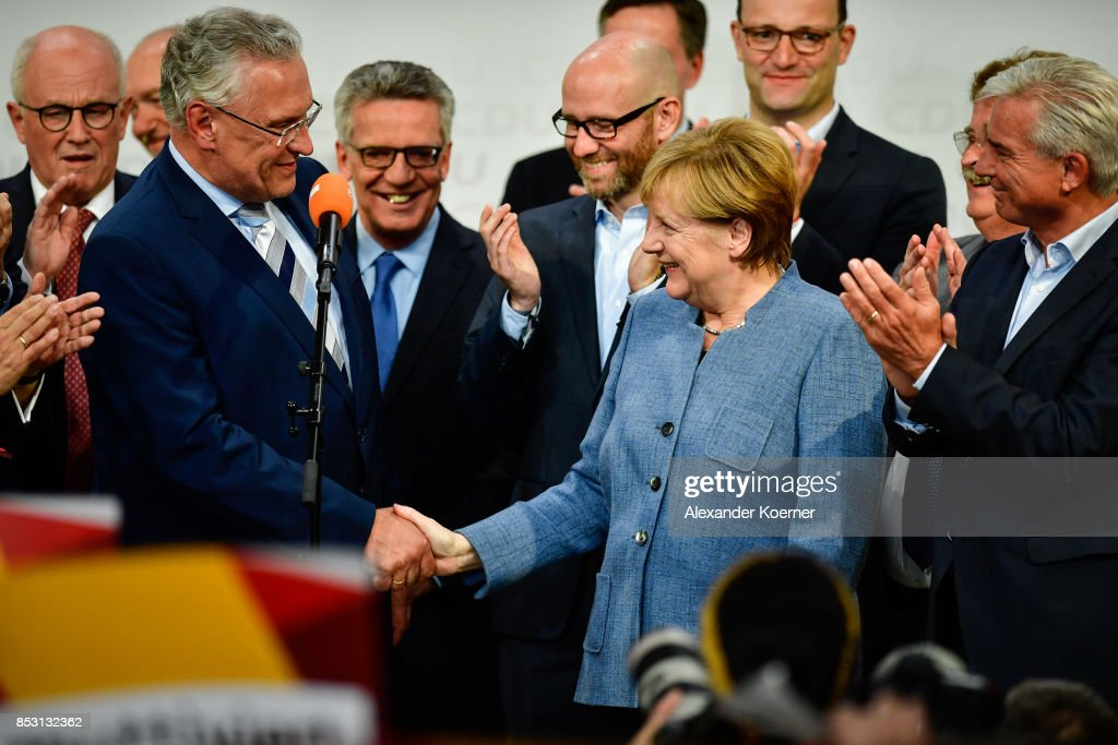 German Chancellor and Christian Democrat (CDU) Angela Merkel (R), Joachim Herrmann (L) (CSU) and other members of CDU react to initial results that give the party 33% of the vote, giving it a first place finish, in German federal elections on September 24, 2017 in Berlin, Germany. Chancellor Merkel is seeking a fourth term and coming weeks will likely be dominated by negotiations between parties over the next coalition government.