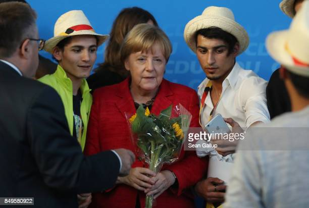 German Chancellor and Christian Democrat Angela Merkel poses for a photo with Syrian refugees after she spoke at an election campaign stop on...