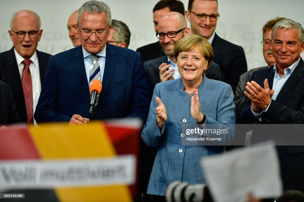 German Chancellor and Christian Democrat (CDU) Angela Merkel (C) reacts to initial results that give the party 33,1% of the vote, giving it a first place finish, in German federal elections on September 24, 2017 in Berlin, Germany. Chancellor Merkel is seeking a fourth term and coming weeks will likely be dominated by negotiations between parties over the next coalition government.
