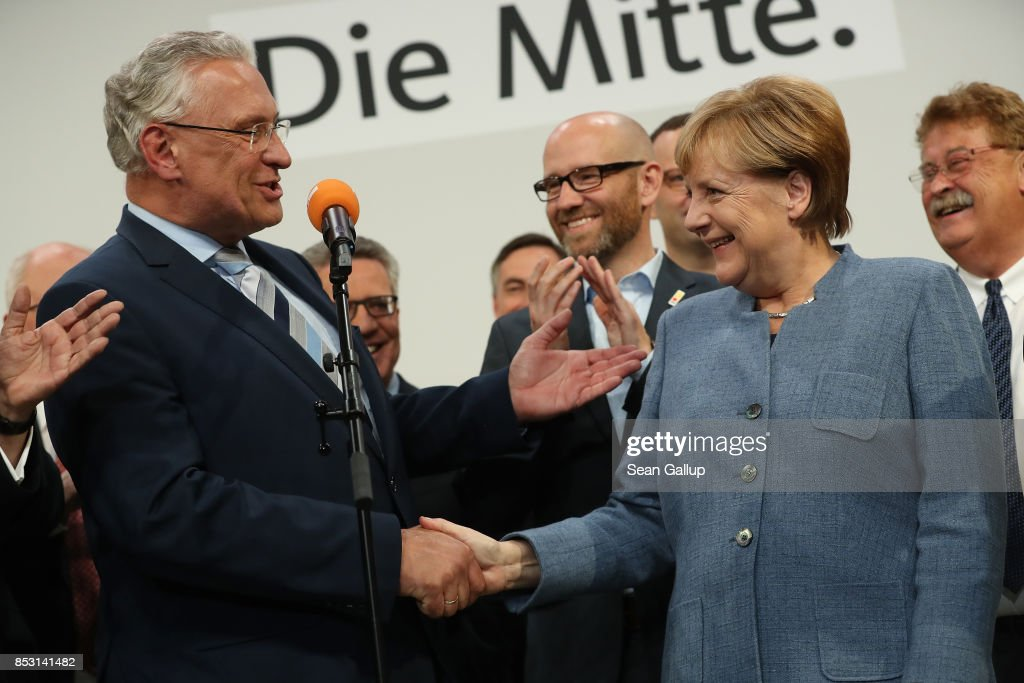 German Chancellor and Christian Democrat (CDU) Angela Merkel (R) shakes hands with leading member of the Bavarian Chrisitan Democrats (CSU) Joachim Herrmann at CDU headquarters at the end of the election evening following federal elections results that give the CDU 33% of the vote, giving it a first place finish, though 8.5% less than in the last election four years ago, on September 24, 2017 in Berlin, Germany. Chancellor Merkel is seeking a fourth term and coming weeks will likely be dominated by negotiations between parties over the next coalition government. The right-wing Alterniative for Germany (AfD) finished in the third place with a better-than-expected 13.2%.