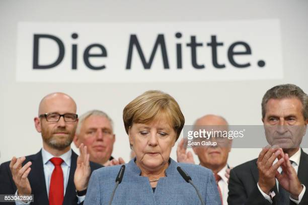 German Chancellor and Christian Democrat Angela Merkel speaks to supporters while standing next to leading members of her party following initial...