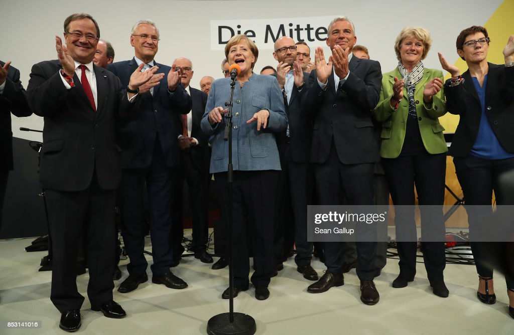 German Chancellor and Christian Democrat (CDU) Angela Merkel (C), standing with leading members of both the CDU and the Bavarian Chrisitan Democrats (CSU), speaks to supporters at CDU headquarters at the end of the election evening following federal elections results that give the CDU 33% of the vote, giving it a first place finish, though 8.5% less than in the last election four years ago, on September 24, 2017 in Berlin, Germany. Chancellor Merkel is seeking a fourth term and coming weeks will likely be dominated by negotiations between parties over the next coalition government. The right-wing Alterniative for Germany (AfD) finished in the third place with a better-than-expected 13.2%.
