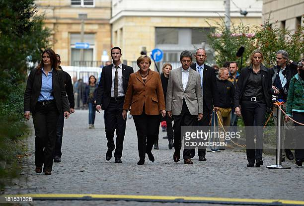 German Chancellor and Christian Democratic Union candidate Angela Merkel and husband Joachim Sauer walk to the polling station in Berlin on September...