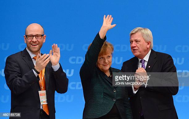 German Chancellor and Christian Democratic Union head Angela Merkel is applauded by the CDU's secretary general Peter Tauber and Hesse's State...