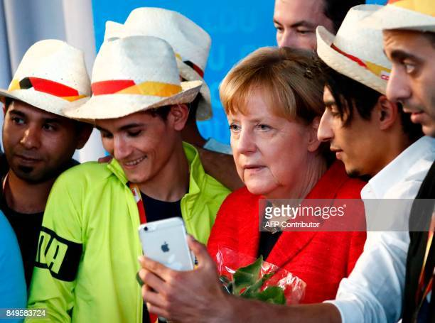 German Chancellor and Christian Democratic Union's main candidate Angela Merkel poses for selfies with Syrian refugees after she gave a speech during...