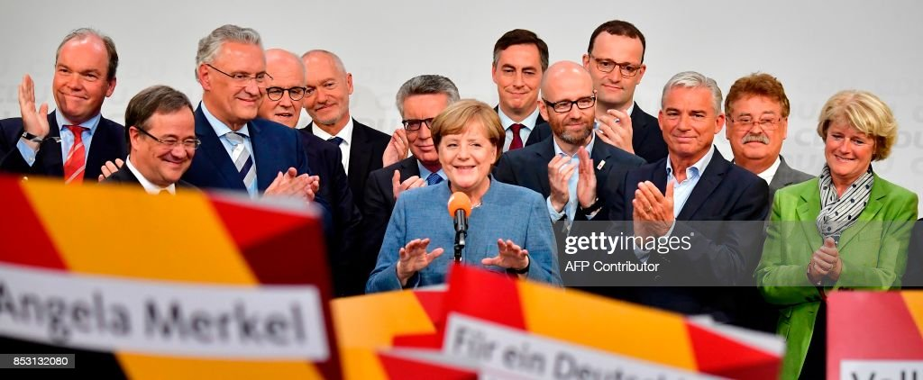 German Chancellor and Christian Democrats party (CDU) leader Angela Merkel (C) is back on stage after attending a television debate during the election night event at the CDU party's headquarters in Berlin during the general election on September 24, 2017. Chancellor Angela Merkel clinched a fourth term in Germany's election, but her victory was clouded by the hard-right AfD party winning its first seats in parliament. / AFP PHOTO / Tobias SCHWARZ