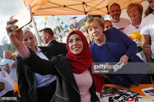 German Chancellor and Chrstian Democrat Angela Merkel poses for a selfie with a young woman who came one year ago from Iran during a brief visit by...