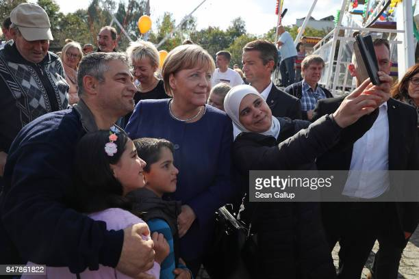 German Chancellor and Chrstian Democrat Angela Merkel poses for a selfie with a Muslim family during a brief visit by Merkel to a local CDUorganized...