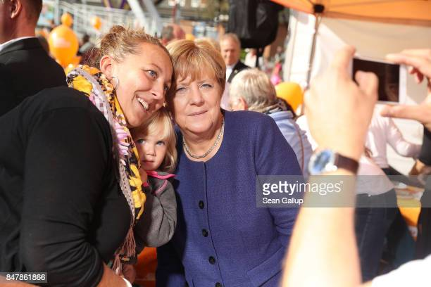 German Chancellor and Chrstian Democrat Angela Merkel poses for a selfie with a a family during a brief visit by Merkel to a local CDUorganized fest...
