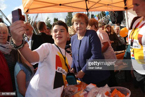German Chancellor and Chrstian Democrat Angela Merkel poses for a selfie with a young visitor during a brief visit by Merkel to a local CDUorganized...