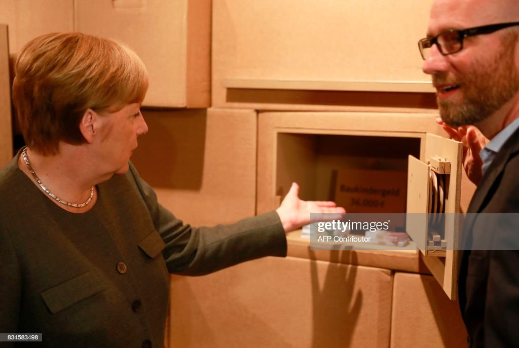 German Chancellor and head of the Christian Democrats party Angela Merkel (L) and CDU Secretary General Peter Tauber show a mock safe as an exhibit during the opening of the so-called 'walkable campaigning program' in Berlin, on August 18, 2017. / AFP PHOTO / Odd ANDERSEN