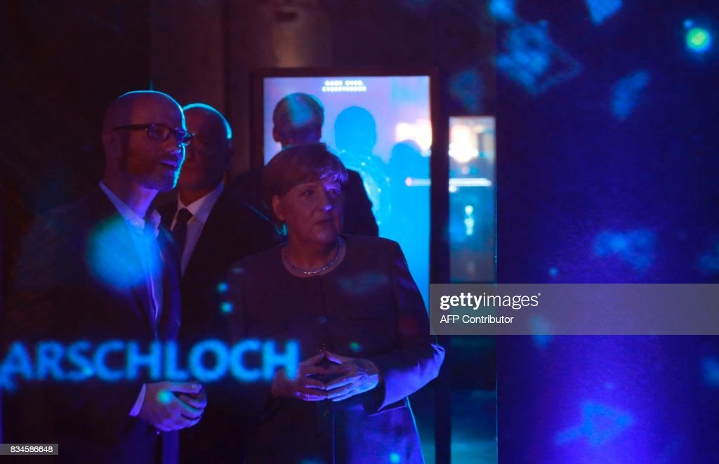 German Chancellor and head of the Christian Democrats party Angela Merkel (R) and CDU Secretary General Peter Tauber watch an exhibit on cyber-mobbing during the opening of the so-called 'walkable campaigning program' in Berlin, on August 18, 2017. / AFP PHOTO / Odd ANDERSEN