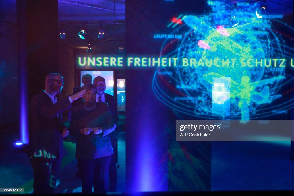 German Chancellor and head of the Christian Democrats party Angela Merkel (R) and CDU Secretary General Peter Tauber watch an exhibit on cyber-mobbing during the opening ceremony of the CDU election campaign exhibition, so-called walkable campaigning program (Das Begehbare Programm) in Berlin, on August 18, 2017. / AFP PHOTO / Odd ANDERSEN