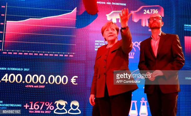 German Chancellor and head of the Christian Democrats party Angela Merkel and CDU Secretary General Peter Tauber stand in front a wall displaying...