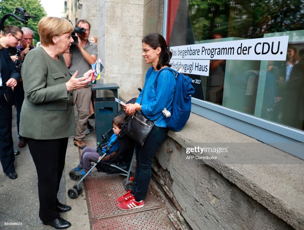 German Chancellor and head of the Christian Democrats party Angela Merkel canvasses in front of the house exhibiting the so-called 'walkable campaigning program' in Berlin, on August 18, 2017. / AFP PHOTO / Odd ANDERSEN