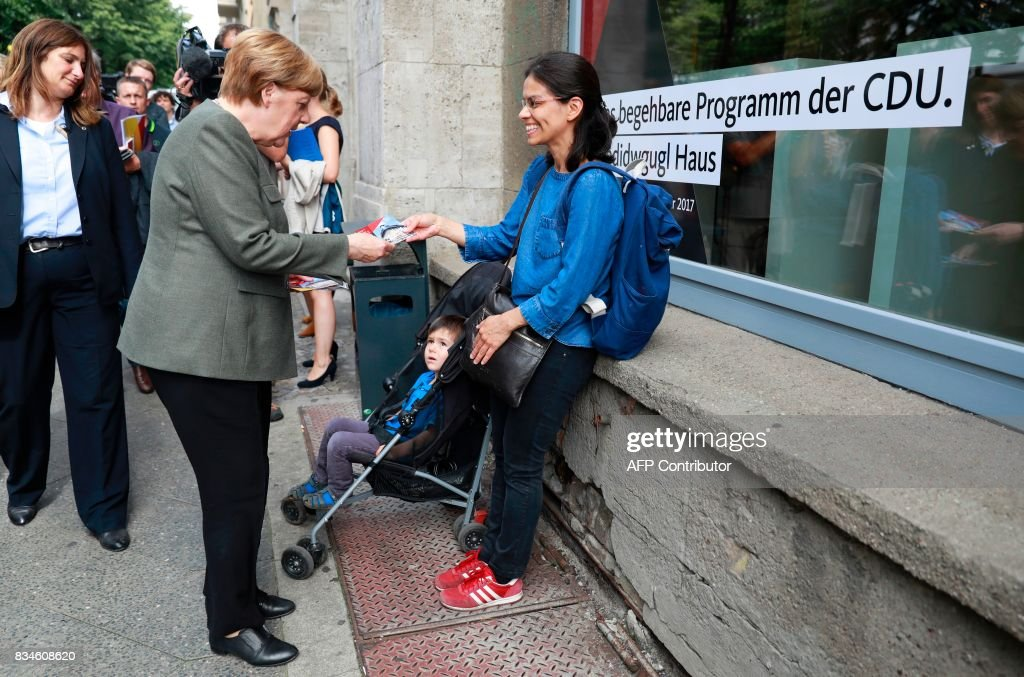 German Chancellor and head of the Christian Democrats party Angela Merkel (2L) canvasses in front of the house exhibiting the so-called 'walkable campaigning program' in Berlin, on August 18, 2017. / AFP PHOTO / Odd ANDERSEN