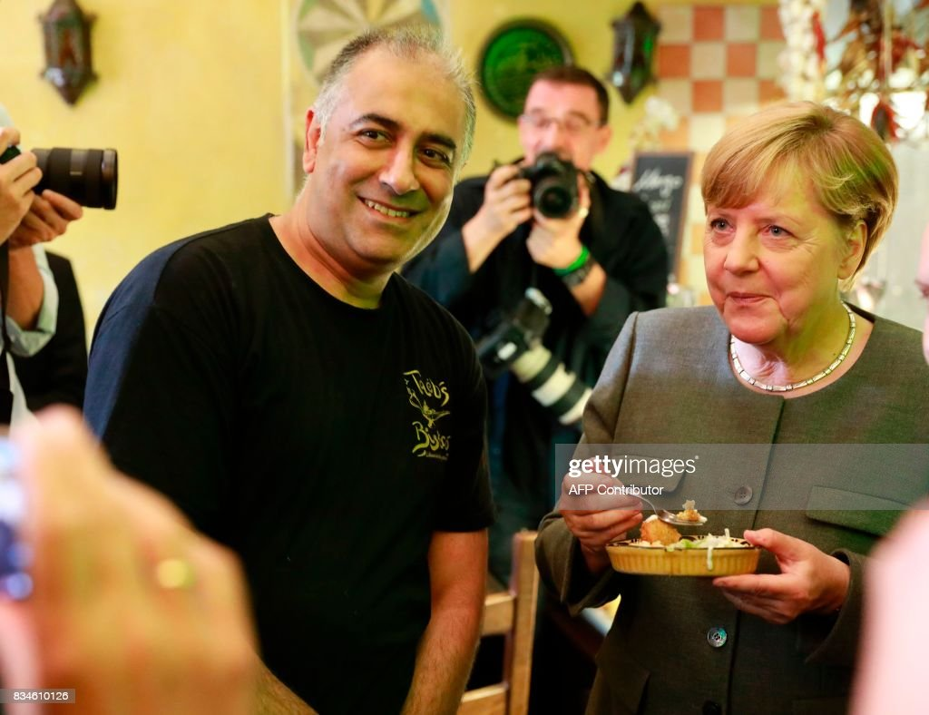 German Chancellor and head of the Christian Democrats party Angela Merkel poses for photographers as she visits some shops in Berlin- Mitte district after the opening of the so-called 'walkable campaigning program' in Berlin, on August 18, 2017. / AFP PHOTO / Odd ANDERSEN