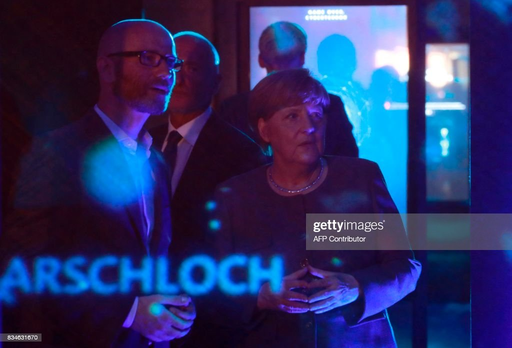 German Chancellor and head of the Christian Democrats party Angela Merkel (R) and CDU Secretary General Peter Tauber watch an exhibit on cyber-mobbing during the opening of the so-called 'walkable campaigning program' in Berlin, on August 18, 2017. / AFP PHOTO / Odd ANDERSEN / ALTERNATIVE
