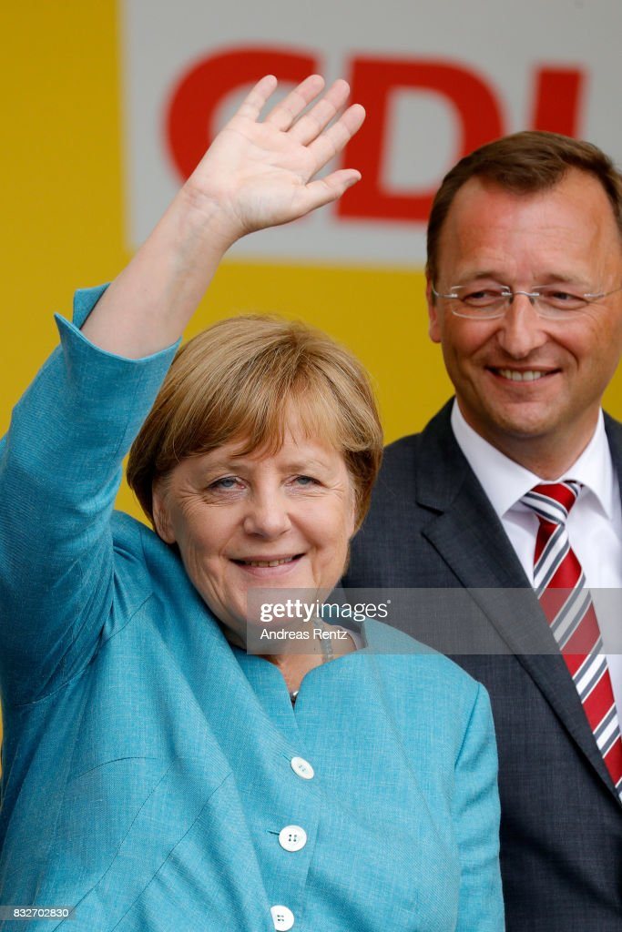 German Chancellor and head of the German Christian Democrats (CDU) Angela Merkel and Josef Oster, candidate for the German parliament, greet supporters after an election rally at the headland known as the 'Deutsches Eck' ('German Corner'), where the Mosel and Rhine rivers meet, on August 16, 2017 in Koblenz, Germany. Germany is scheduled to hold federal elections on September 24 and Merkel, who is running for a fourth term as chancellor, currently holds a double-digit lead over Martin Schulz from the German Social Democrats (SPD), her main opponent.