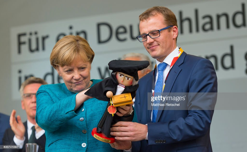 German Chancellor and head of the German Christian Democrats (CDU) Angela Merkel, left, is handed a nut cracker in person of reformator Martin Luther by Alexander Krauss after her speech at an election rally in the state of Saxony on August 17, 2017 in Annaberg-Buchholtz, Germany. Germany is scheduled to hold federal elections on September 24 and Merkel, who is running for a fourth term as chancellor, currently holds a double-digit lead over Martin Schulz from the German Social Democrats (SPD), her main opponent.