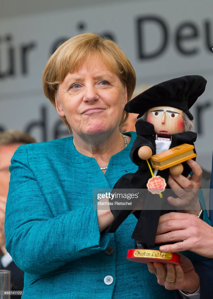 German Chancellor and head of the German Christian Democrats (CDU) Angela Merkel, left, is handed a nut cracker in person of reformator Martin Luther after her speech on an election rally in the state of Saxony on August 17, 2017 in Annaberg-Buchholtz, Germany. Germany is scheduled to hold federal elections on September 24 and Merkel, who is running for a fourth term as chancellor, currently holds a double-digit lead over Martin Schulz from the German Social Democrats (SPD), her main opponent.