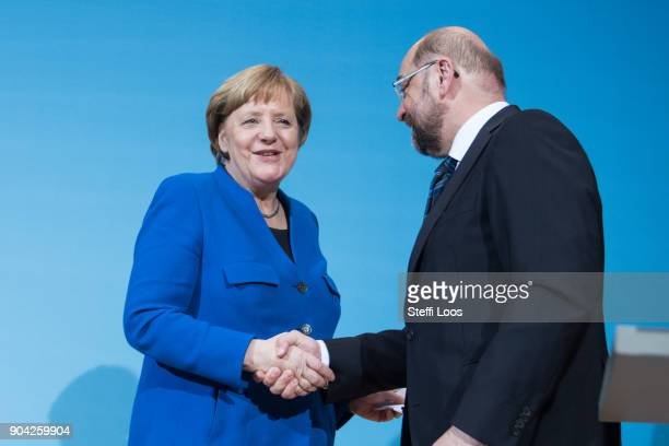 German Chancellor and head of the German Christian Democrats Angela Merkel and leader of the German Social Democrats Martin Schulz shake hands after...