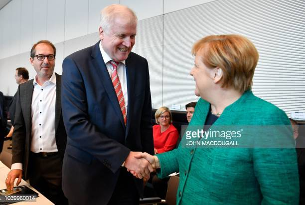 German Chancellor and leader of the Christian Democratic Union Angela Merkel shakes hands with German Interior Minister Horst Seehofer under dthe...