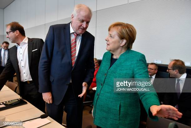 German Chancellor and leader of the Christian Democratic Union Angela Merkel confers with German Interior Minister Horst Seehofer under the eyes of...