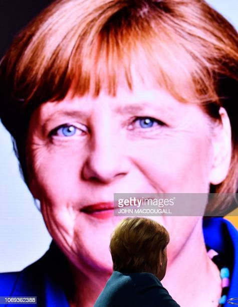 German Chancellor and leader of the Christian Democratic Union Angela Merkel looks at a remembrance video about herself at a party congress of...