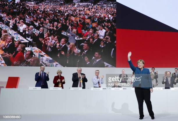 TOPSHOT German Chancellor and leader of the Christian Democratic Union Angela Merkel waves as party members applaud after her speech at a party...