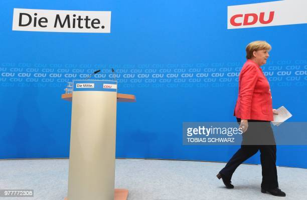 TOPSHOT German Chancellor and leader of the Christian Democratic Union Angela Merkel leaves after addressing a press conference following a party...