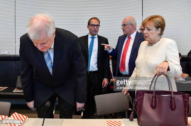 German Chancellor and leader of the Christian Democratic Union Angela Merkel watches as German Interior Minister and leader of the Bavarian Christian...